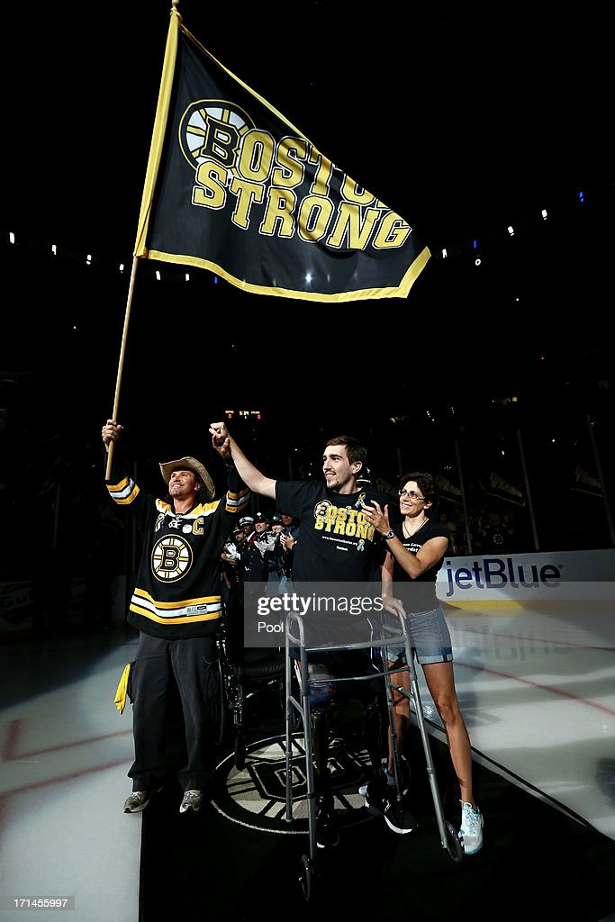 Boston Marathon bombing victim, Jeff Bauman (C), holds the hand of Carlos Arredondo (L), the man who came to his aid immediately following the explosions, after being wheeled out to wave the Boston Strong Flag prior to Game Six of the 2013 NHL Stanley Cup Final between the Chicago Blackhawks and the Boston Bruins at TD Garden on June 24, 2013 in Boston, Massachusetts.