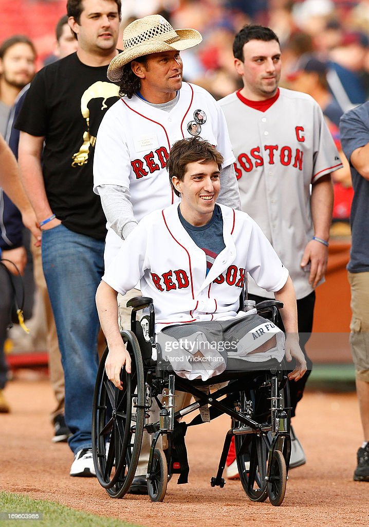 Boston Marathon bombing victim, Jeff Bauman, is wheeled out to the pitchers mound before throwing out the ceremonial first pitch by Carlos Arredondo, the man who came to his aid immediately following the explosions, prior to the interleague game between the Boston Red Sox and the Philadelphia Phillies on May 28, 2013 at Fenway Park in Boston, Massachusetts.