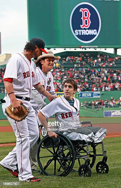 Boston Marathon bombing victim Jeff Bauman threw out a ceremonial first pitch before the game joined on the field by the man credited with saving his...
