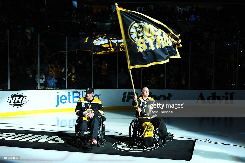 Boston Marathon victims JP and Paul Norden wave the fan banner before the game of the Boston Bruins against the New York Rangers in Game Five of the Eastern Conference Semifinals during the 2013 NHL Stanley Cup Playoffs at TD Garden on May 25, 2013 in Boston, Massachusetts.
