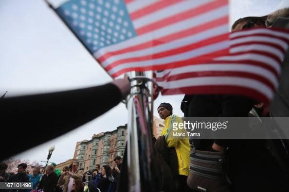 2013 Boston Marathon volunteer Lydia C wears a marathon jacket while she visits a makeshift memorial for victims near the site of the Boston Marathon...