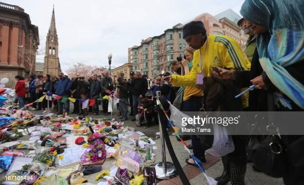 Boston Marathon volunteer Lydia wears a marathon jacket while she visits a makeshift memorial for victims near the site of the Boston Marathon...