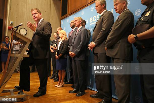 Boston Mayor Martin Walsh speaks at the podium along with Governor Charlie Baker and other city and state officials during a press conference at City...