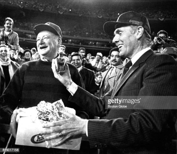 Boston Mayor Ray Flynn right holds a roast beef sandwich from New York City Mayor Ed Koch left during Game One of the 1986 World Series between the...