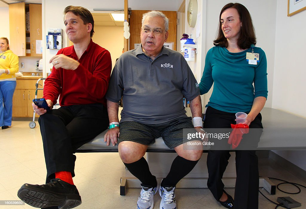 Boston Mayor Thomas Menino continues his physical therapy at Spaulding Rehabilitation Hospital as he has a visit with Boston Pops conductor Keith Lockhart, left, who clicks his fingers to a Christmas song. His physical therapist, Cara Brickley, right, looks pauses her work with him.