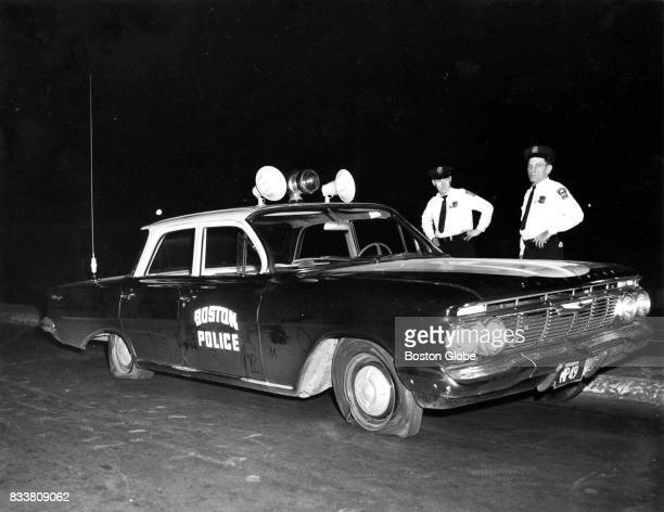 Boston Police cruiser is pictured on Columbus Avenue with three flat tires after going over a curb to cut off a car being chased on Aug 25 1961