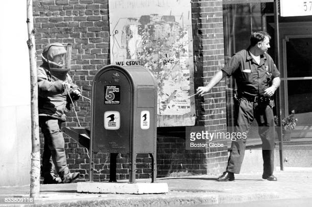 Boston Police Department bomb squad members Jim Bonner and John Kennedy prepare to pull a device from a mailbox at Upham's Corner in the Dorchester...