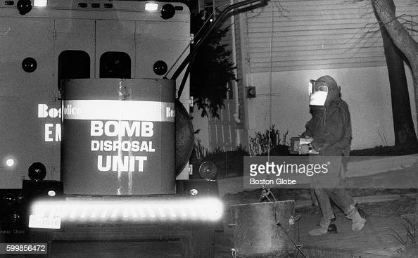 Boston Police Department bomb technician Bob Thistle removes one of the several homemade explosive devices found at 116 Alabama St in the Roxbury...