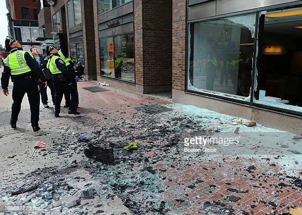 Boston Police look at blown out windows at the scene of the first explosion on Boylston Street near the finish line of the Boston Marathon