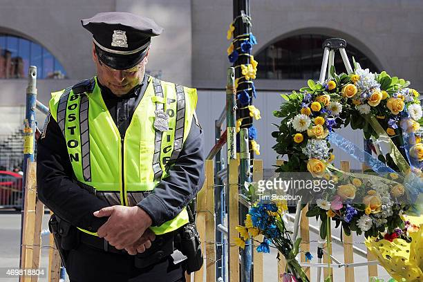 Boston police officer Roy Broussard observes a moment of silence at 249 pm ET near the finish line of the Boston Marathon on Boylston Street...