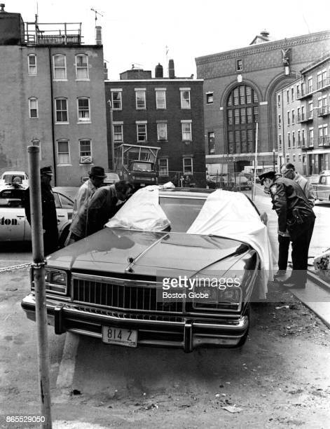 Boston Police officers investigate the scene of a murder in a parking lot in the North End of Boston on Mar 30 1976 The body of Patrick J Fabiano of...