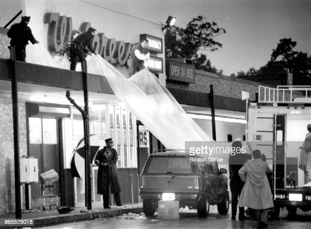 Boston Police officers shield Detective John J Mulligan's vehicle with a tarp to protect evidence in the investigation of his murder outside of a...
