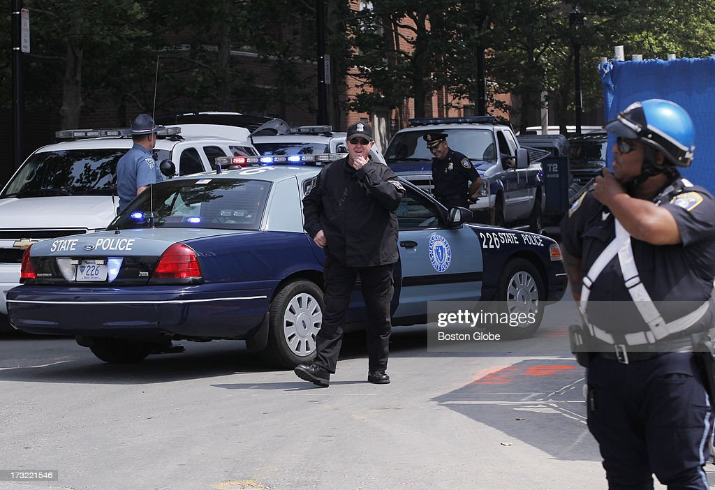 Boston Police officers stand watch as a motorcade carries alleged Boston Marathon bomber Dzhokhar Tsarnaev arrives at the John Joseph Moakley Courthouse in Boston, July 10, 2013.