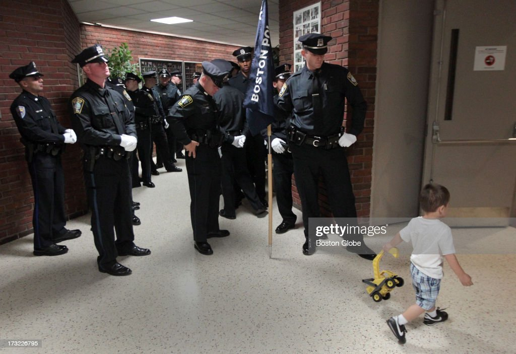 Boston Police recruit Ryan Connolly, at right, waits with other recruits before the Boston Police Academy Graduation at the I.B.E.W. Hall on Freeport Street in Dorchester. Manny Aguliar with toy truck was attending for his uncle who was graduating.