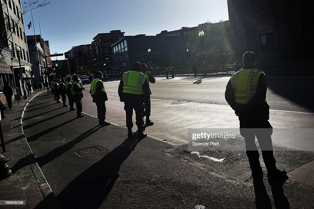 Boston police wait for President Barack Obama's motorcade before he speaks at an interfaith prayer service for victims of the Boston Marathon attack titled 'Healing Our City,' at the Cathedral of the Holy Cross on April 18, 2013 in Boston, Massachusetts. Authorities investigating the attack on the Boston Marathon have shifted their focus to locating the person who placed a black bag down and walked away just before the bombs went off. The twin bombings at the 116-year-old Boston race, which occurred near the marathon finish line, resulted in the deaths of three people and more than 170 others injured.