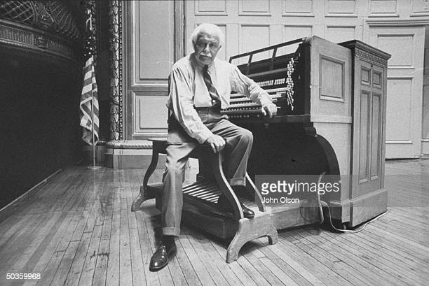 Boston Pops conductor Arthur M Fiedler sitting at the keyboard of a large organ