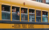 Boston Public School bus with elementary school children look out their windows at the shooting scene and media as their bus passes near the Jeremiah...
