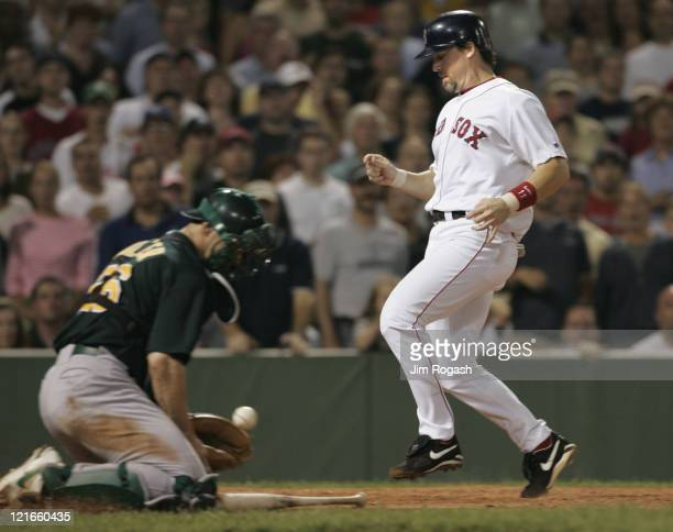 Boston Red Sox base runner Bill Mueller right scores as Oakland Athletics catcher Damian Miller fields a late throw to the plate at Fenway Park in...