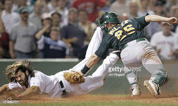 Boston Red Sox base runner Johnny Damon left avoids the tag Oakland Athletics catcher Damian Miller to score the winning run at Fenway Park in Boston...