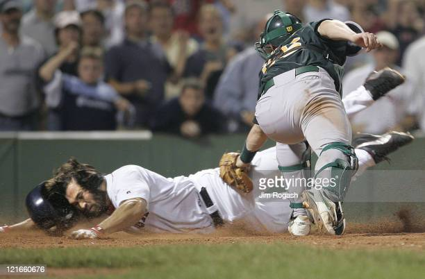 Boston Red Sox base runner Johnny Damon left eludes the tag Oakland Athletics catcher Damian Miller to score the winning run at Fenway Park in Boston...