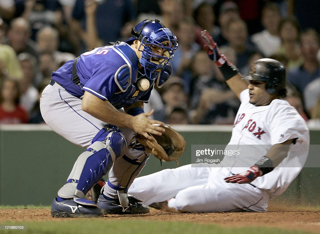 Boston Red Sox base runner Manny Ramirez, right, scores as Texas Rangers catcher Rod Barajas loses control of the ball Friday, July 9, 2004. The Red Sox won 7-0 at Fenway Park in Boston.