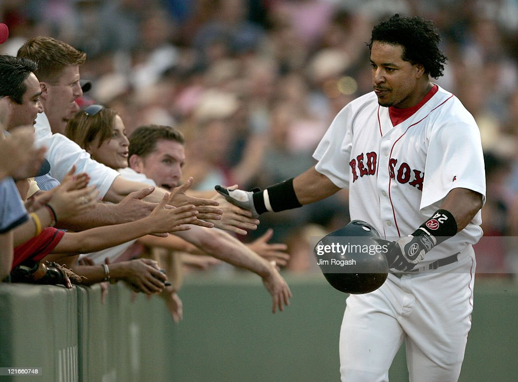 Boston Red Sox batter Manny Ramirez touches the hands of fans after he hit the first of two home runs against Texas Rangers, Saturday, July 10, 2004. The Red Sox won 14-6 at Fenway Park in Boston.