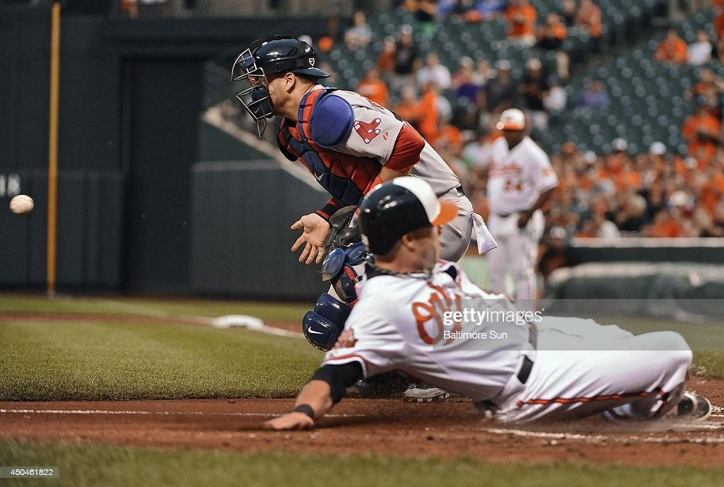 Boston Red Sox catcher A.J. Pierzynski, top, waits for the ball as the Baltimore Orioles' Steve Pearce slides home to score on a double by Adam Jones in the first inning at Oriole Park at Camden Yards in Baltimore on Wednesday, June 11, 2014.