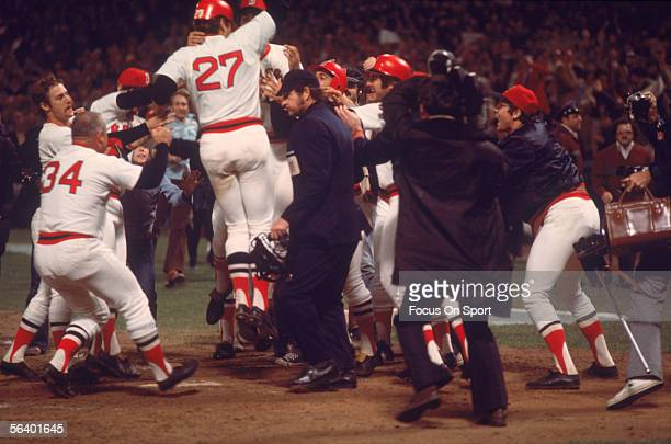 Boston Red Sox' catcher Carlton Fisk runs to home and is met by his teammates after hitting a home run against the Cincinnati Reds in the 12th inning...