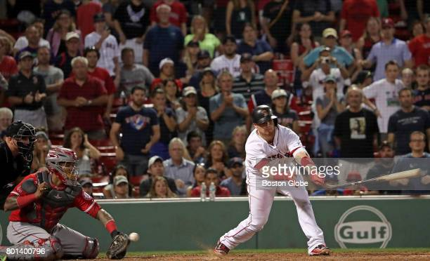 Boston Red Sox catcher Christian Vazquez swings and loses his bat but the ball gets past Los Angeles Angels catcher Martin Maldonado scoring a run on...