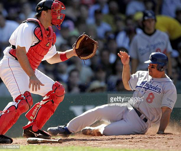 Boston Red Sox catcher Doug Mirabelli left waits for the throw as Los Angeles Dodgers base runner Olmedo Saenz scores a run at Fenway Park in Boston...