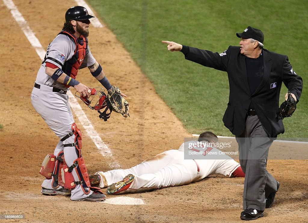 Boston Red Sox catcher Jared Saltalamacchia, left, looks to umpire Dana DeMuth as he indicates an obstruction call at third base as Allen Craig of the St. Louis Cardinals is safe at the plate on the ninth-inning play in Game 3 of the World Series on Saturday, October 26, 2013, at Busch Stadium in St. Louis, Missouri. Craig's run was the game-winner in the Cards' 5-4 triumph. .