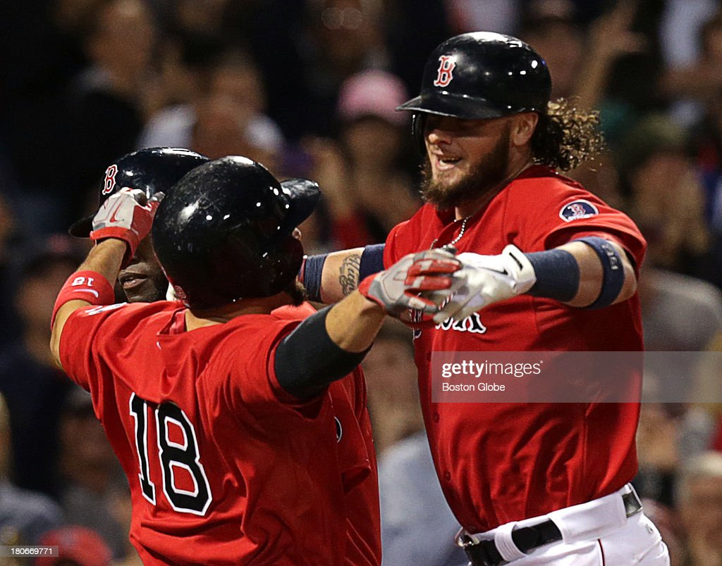 Boston Red Sox catcher Jarrod Saltalamacchia (#39) is greeted by Boston Red Sox right fielder Shane Victorino (#18) as he crosses the plate after his Grand Slam in the seventh inning. The Boston Red Sox take on the New York Yankees in Game one of a three game series at Fenway Park.