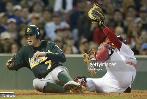 Boston Red Sox catcher Jason Varitek is late with the tag as Oakland Athletics' Bobby Crosby slides safely home Thursday May 27 2004 The Red Sox lost...