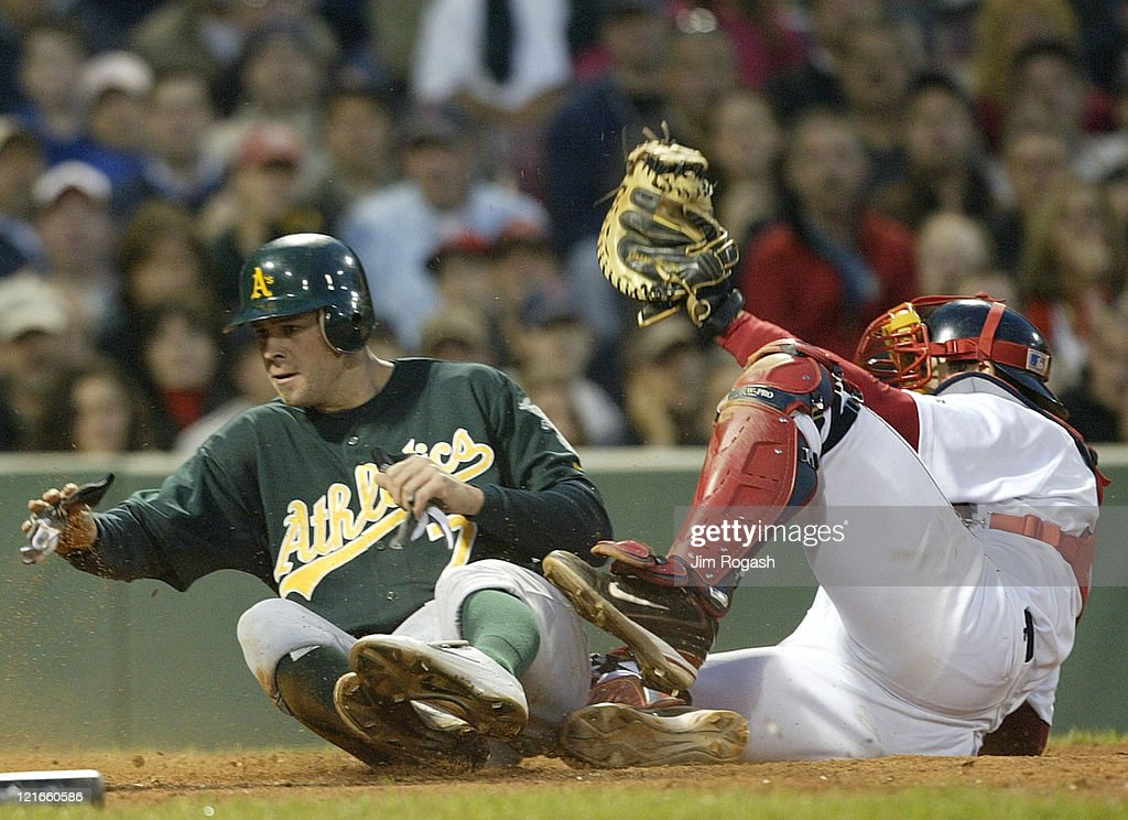 Boston Red Sox catcher <a gi-track='captionPersonalityLinkClicked' href=/galleries/search?phrase=Jason+Varitek&family=editorial&specificpeople=171480 ng-click='$event.stopPropagation()'>Jason Varitek</a> is late with the tag as Oakland Athletics' <a gi-track='captionPersonalityLinkClicked' href=/galleries/search?phrase=Bobby+Crosby&family=editorial&specificpeople=201738 ng-click='$event.stopPropagation()'>Bobby Crosby</a> slides safely home, Thursday, May 27, 2004. The Red Sox lost 15-2 at Fenway Park in Boston, Massachusetts.