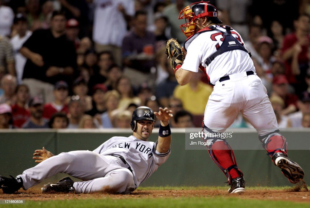 Boston Red Sox catcher Jason Varitek, right is late with the tag as New York Yankees' Jorge Posada scores at Fenway Park in Boston, Massachuesetts on July 23, 2004. The Yankees won 8-7.