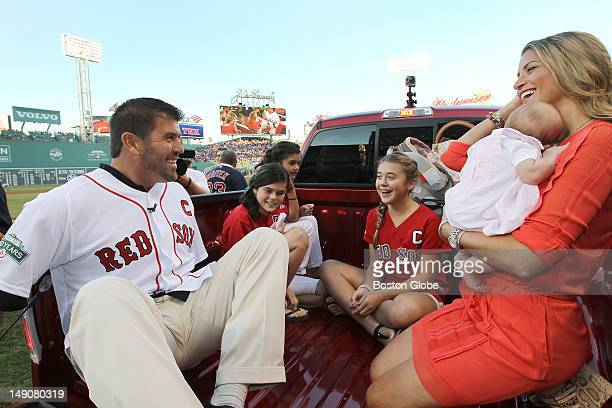 Boston Red Sox catcher Jason Varitek sits in the bed of a new truck given to him by the Boston Red Sox organization accompanied by his wife and...