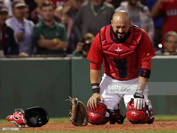 Boston Red Sox catcher Sandy Leon kneels in pain after he was struck by a foul tip during the ninth inning Leon was attended to and then remained in...