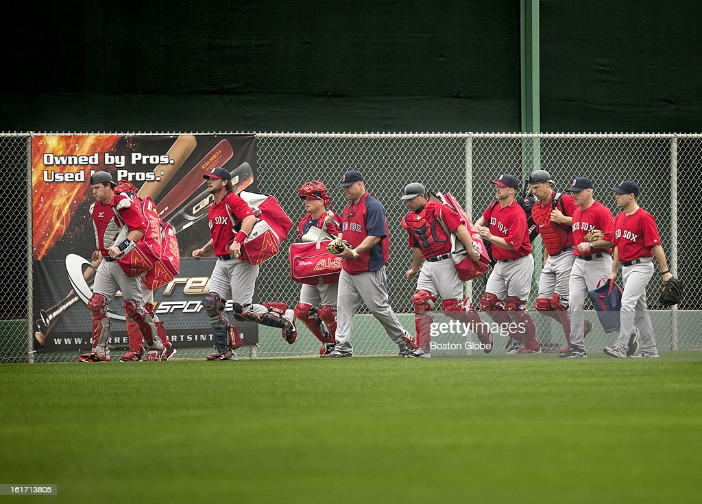 Boston Red Sox catchers jog off the outdoor practice fields to workout in the covered batting cages due to rain. Day three of spring training at the Red Sox training facilities at JetBlue Park on Thursday, Feb. 14, 2013.