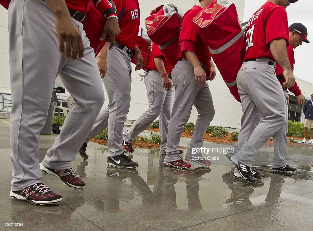 Boston Red Sox catchers walk through puddles as they head to the practice fields. One hour later, due to heavy rain, all practice was done in the covered batting cages. Day three of spring training at the Red Sox training facilities at JetBlue Park on Thursday, Feb. 14, 2013.