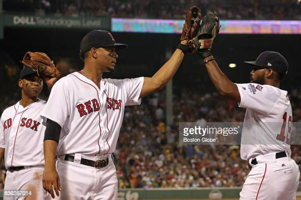 Boston Red Sox center fielder Jackie Bradley Jr gets a high five from Boston Red Sox shortstop Xander Bogaerts after his defensive catch in the...