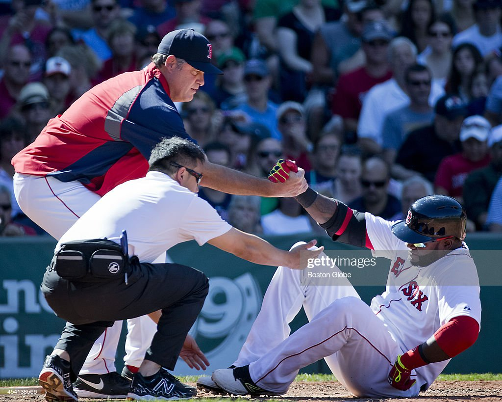 Boston Red Sox David Ortiz getting a hand by their trainer and manager John Farrell after he injures his leg at bat against the Seattle Mariners during fourth inning action at Fenway Park on Sunday, August 24, 2014.