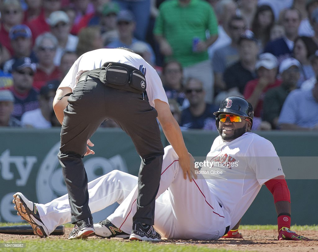 Boston Red Sox David Ortiz getting checked out by their trainer as he injures his leg against the Seattle Mariners during fourth inning action at Fenway Park on Sunday, August 24, 2014.