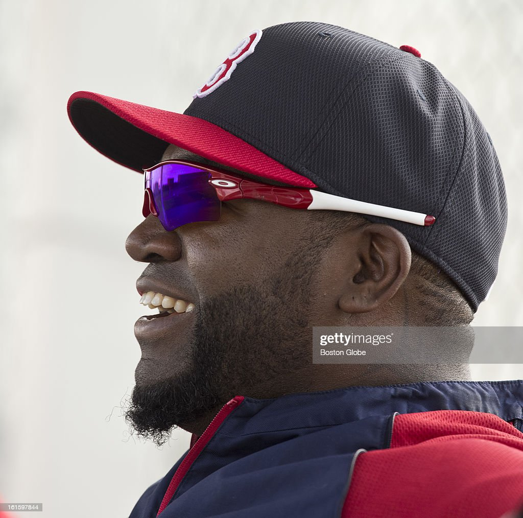 Boston Red Sox David Ortiz laughing while sitting on the bench watching his teammates work out during the first official spring training day for the Boston Red Sox pitchers and catchers at JetBlue Park on Tuesday, Feb. 12, 2013.