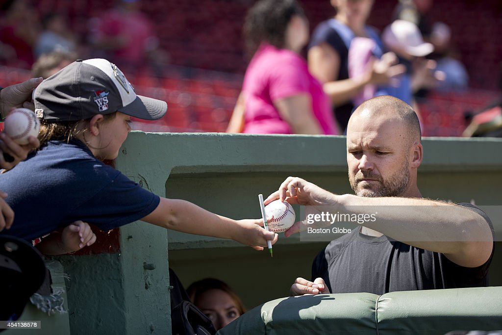 Boston Red Sox David Ross signing his autograph for a fan before the Red Sox play the Seattle Mariners at Fenway Park on Sunday, August 24, 2014.