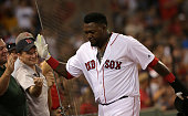 Boston Red Sox designated hitter David Ortiz and fans exchange high fives after Ortiz scored on a RBI double by Boston Red Sox center fielder Jackie...