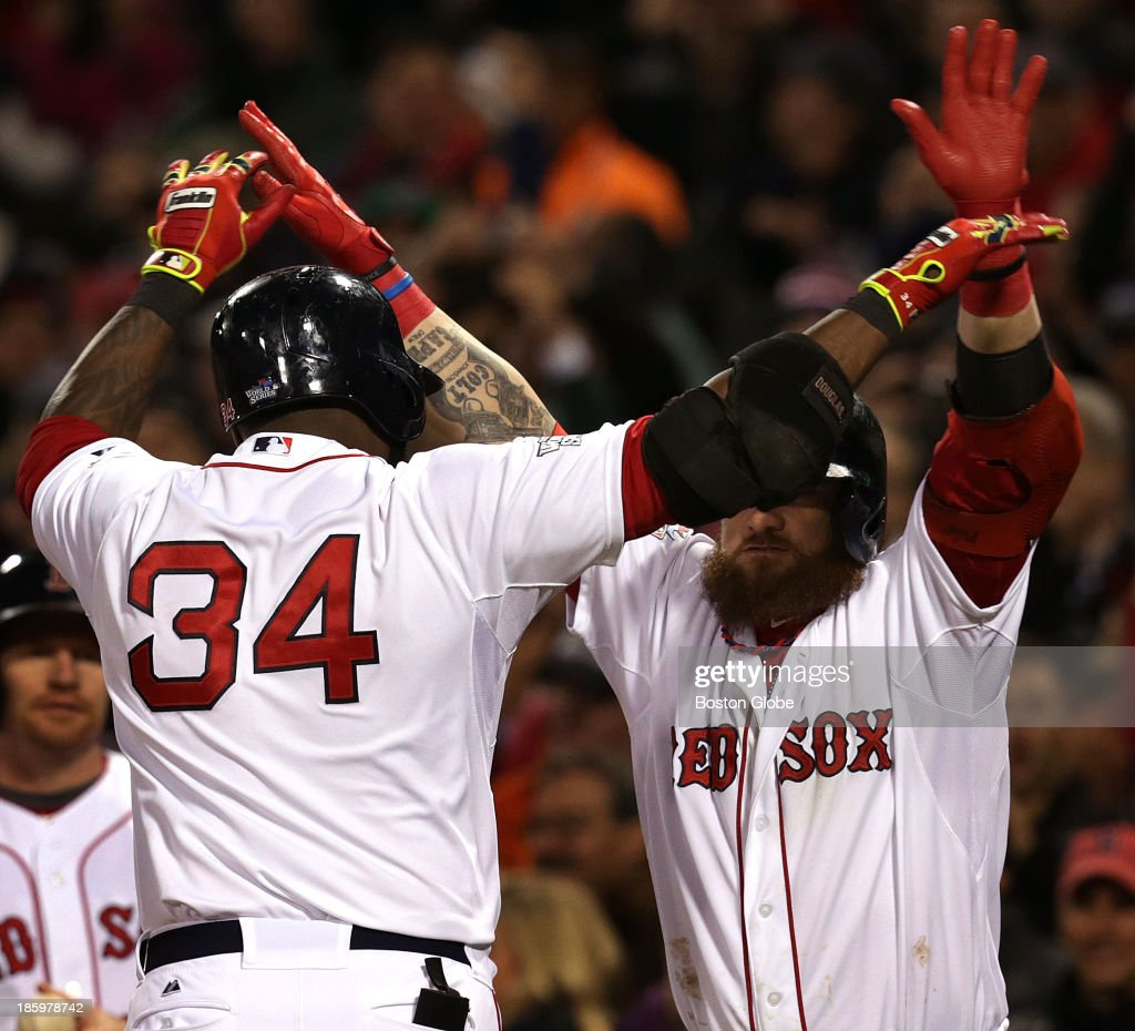 Boston Red Sox designated hitter David Ortiz (#34) is greeted at home plate by Boston Red Sox left fielder Jonny Gomes (#5) after Ortiz's two run home run in the sixth inning. The Boston Red Sox host the St. Louis Cardinals at Fenway Park for Game Two of the 2013 Major League Baseball World Series, Oct. 24, 2013.