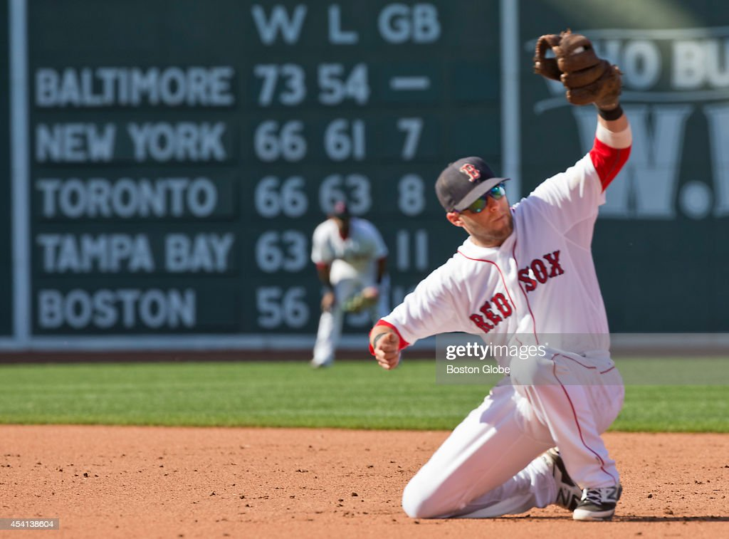 Boston Red Sox Dustin Pedroia snares a hard hit ground ball by Seattle Mariners Dustin Ackley starting a double play during seventh inning action at Fenway Park on Sunday, August 24, 2014.