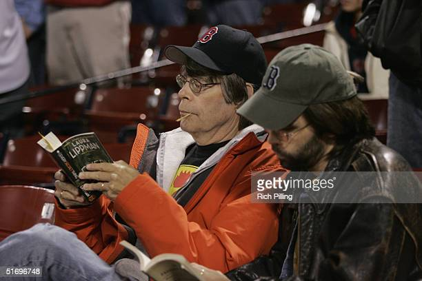 Boston Red Sox fan and novelist Stephen King reads before game three of the ALCS game against the New York Yankees at Fenway Park on October 16 2004...