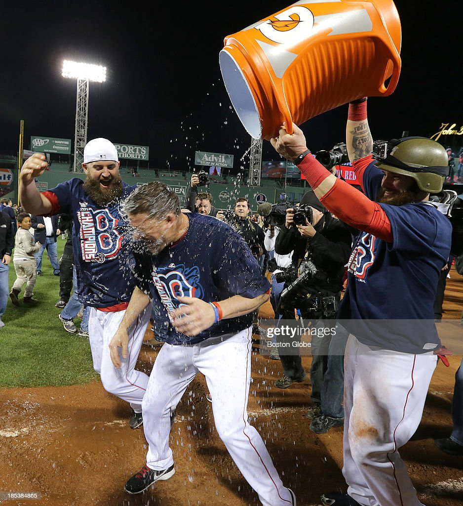 Boston Red Sox first baseman Mike Napoli (#12) and Boston Red Sox left fielder Jonny Gomes (#5) dump a bucket of Gatorade on Boston Red Sox starting pitcher Jake Peavy (#44) as they celebrate on the field. The Boston Red Sox defeated the Detroit Tigers in Game Six of the American League Champion Series at Fenway Park on Oct.19, 2013. The Red Sox will advance to the World Series.