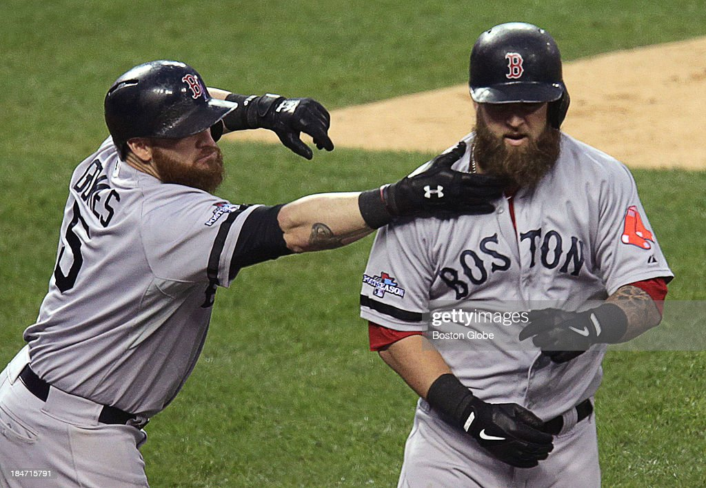 Boston Red Sox first baseman Mike Napoli (#12) gets a celebratory tug on his beard from Boston Red Sox left fielder Jonny Gomes (#5) after his solo home run off Detroit Tigers starting pitcher Justin Verlander (#35) in the seventh inning. The Boston Red Sox visited the Detroit Tigers in Game Three of the American League Champion Series at Comerica Park in Detroit, Mich., Oct. 15, 2013.